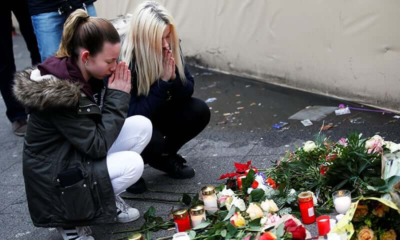 Women mourn at the scene where a truck ploughed into a crowded Christmas market in the German capital last night in Berlin,